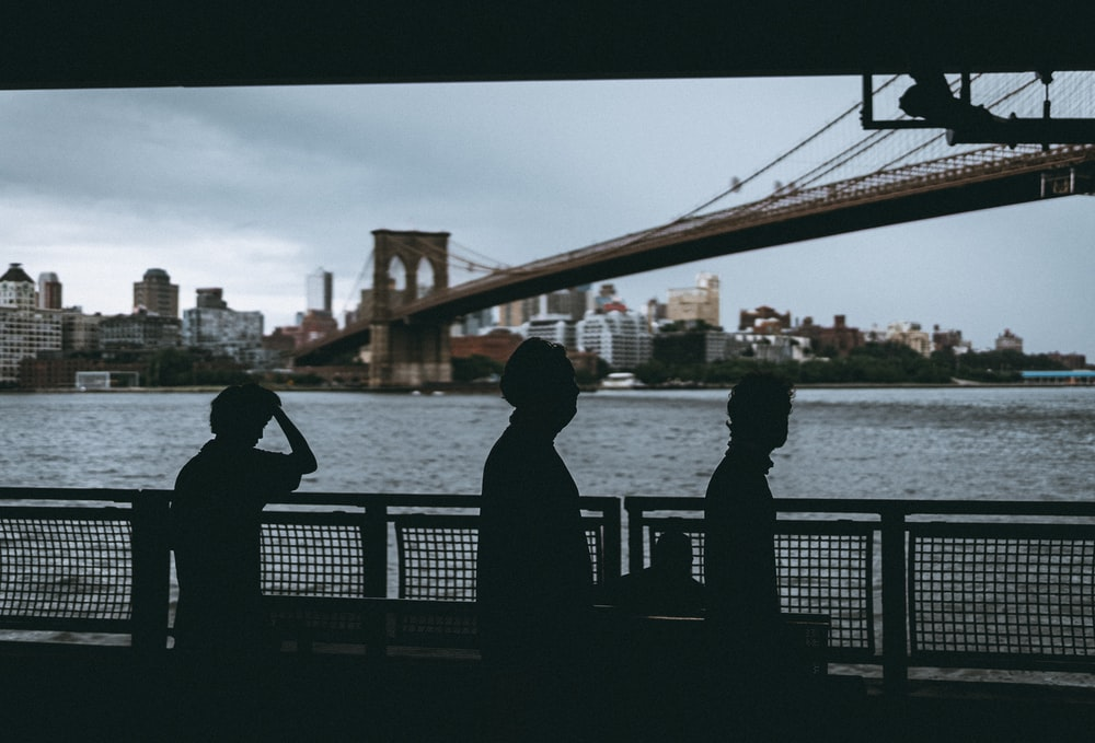 silhouette of couple standing on bridge during daytime