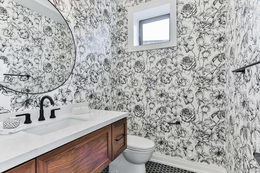 white ceramic sink beside white and black floral wall