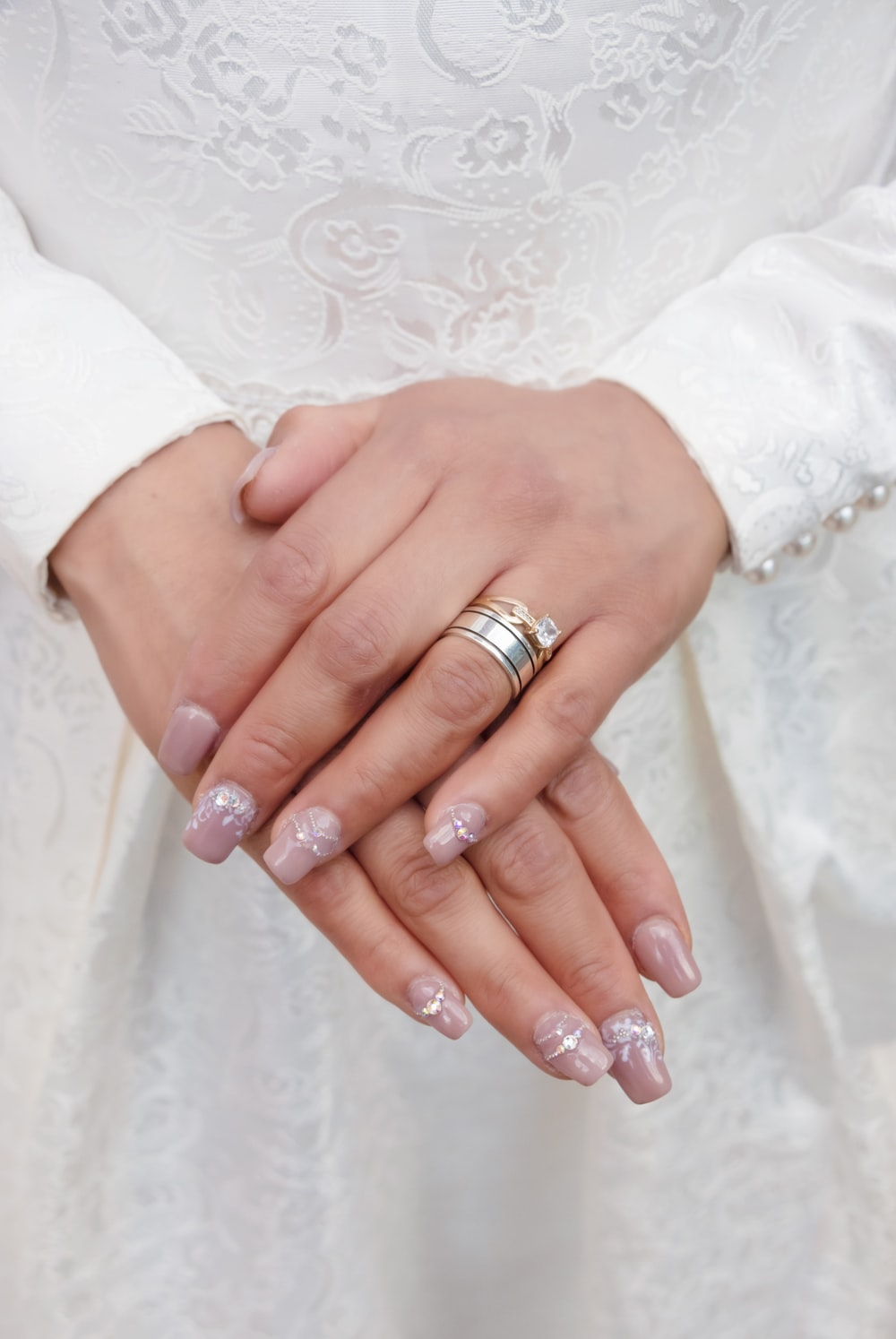 woman wearing silver ring and white floral lace dress
