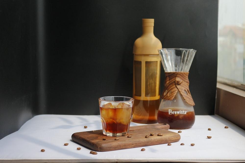 clear drinking glass beside brown bottle