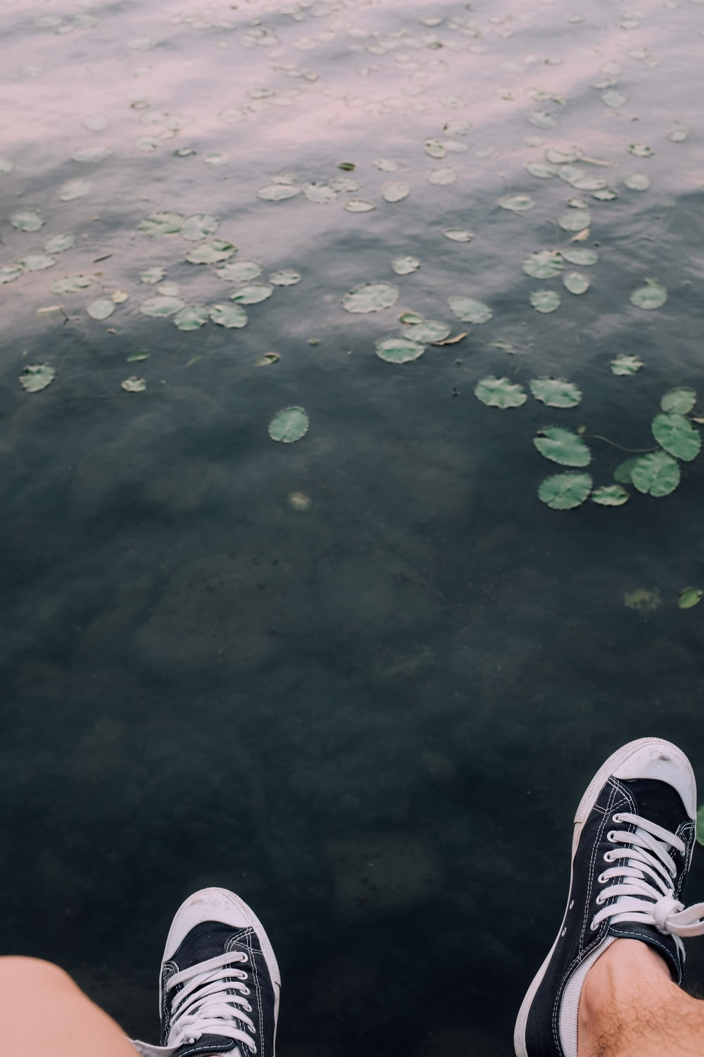 person wearing black and white sneakers standing on water