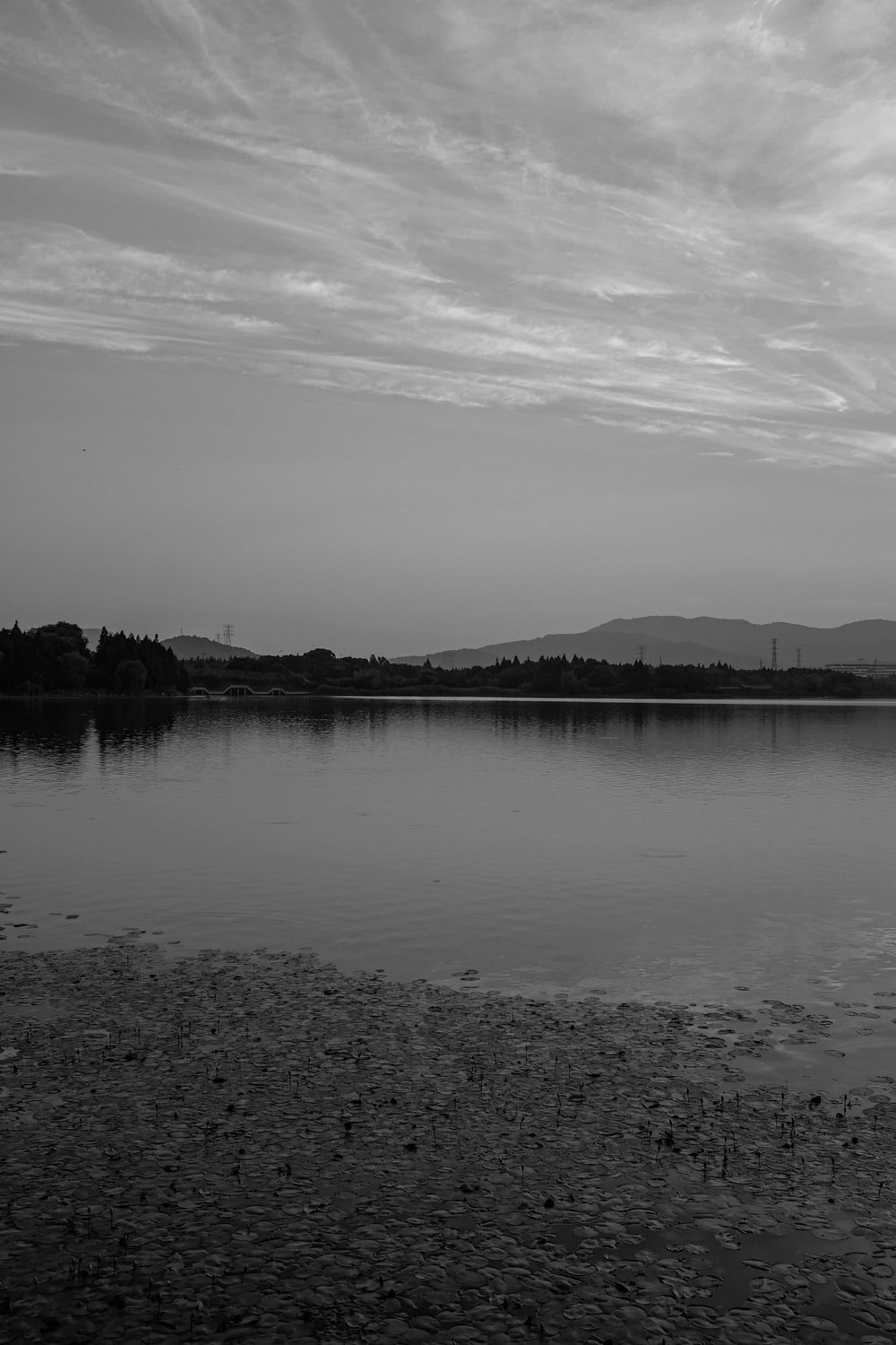 grayscale photo of body of water near mountain