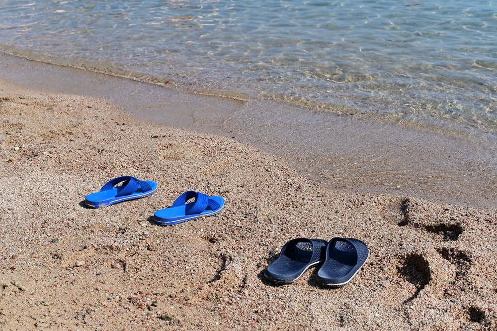 blue and black flip flops on beach