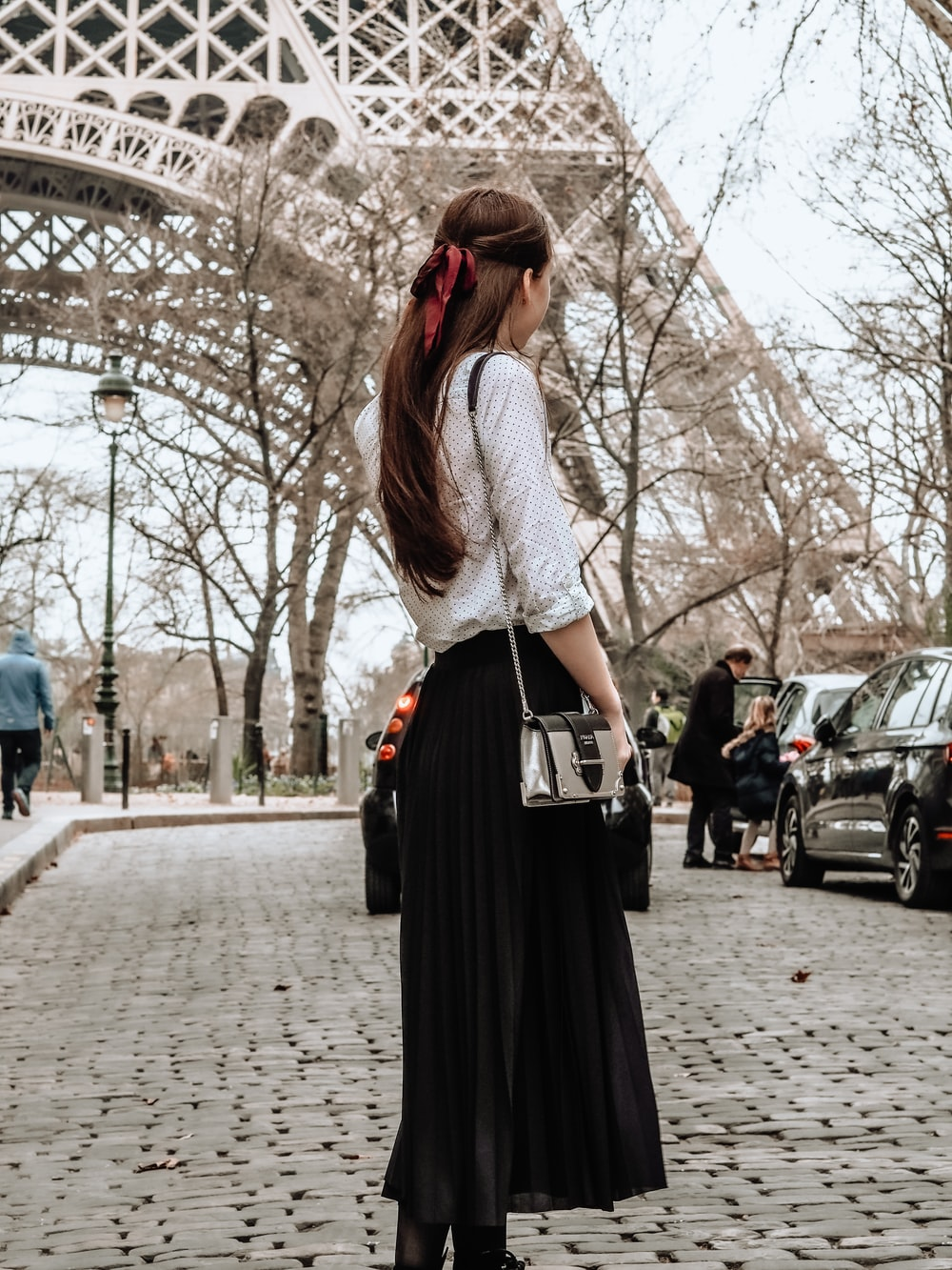 woman in white and black dress standing on sidewalk during daytime
