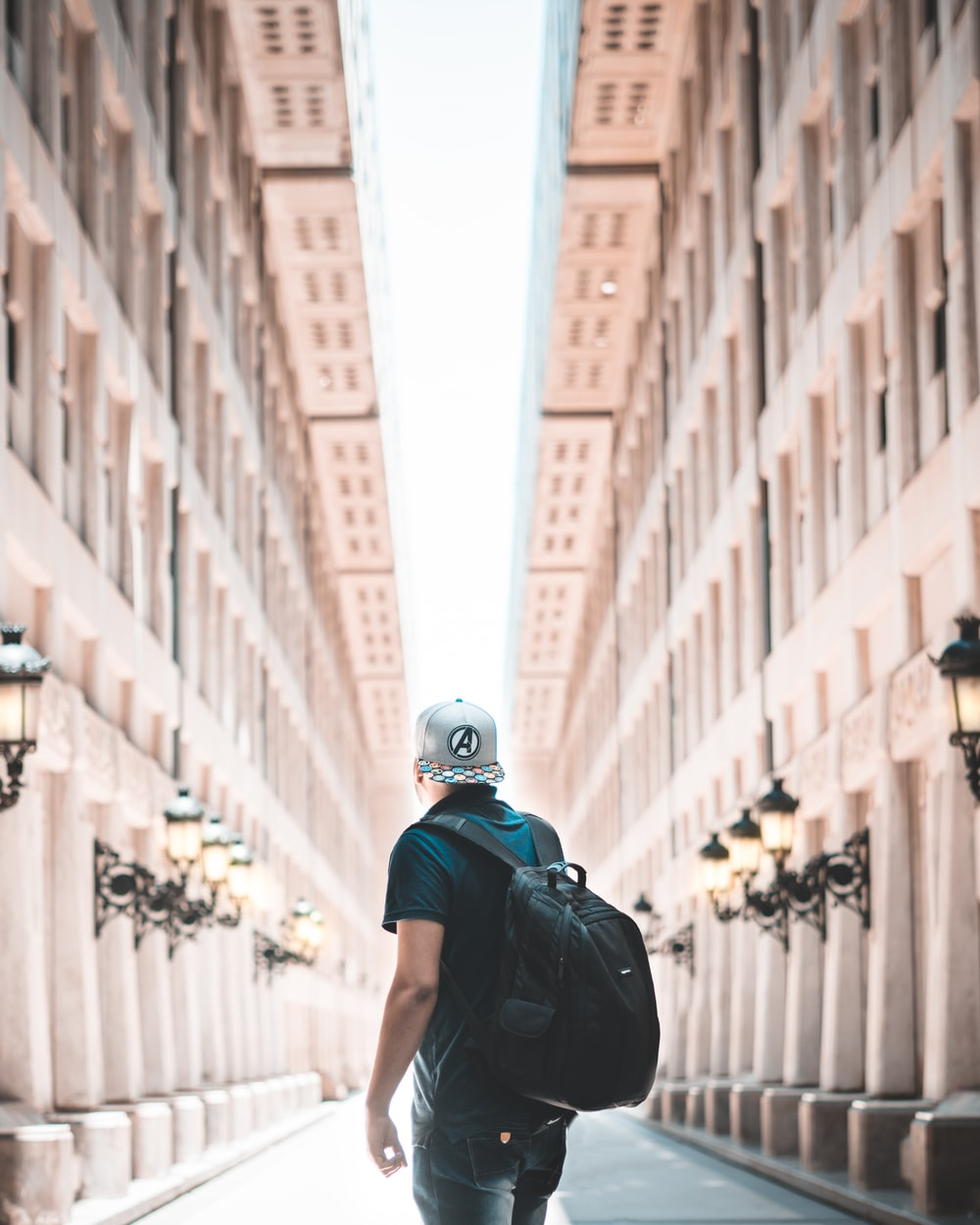 man in black shirt wearing white cap and backpack standing in front of brown concrete building