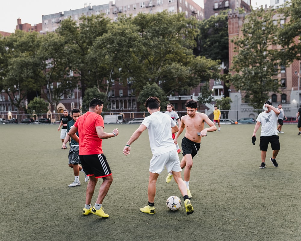 group of people playing soccer on green grass field during daytime