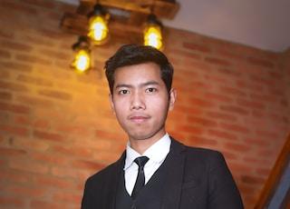 man in black suit standing near brown brick wall