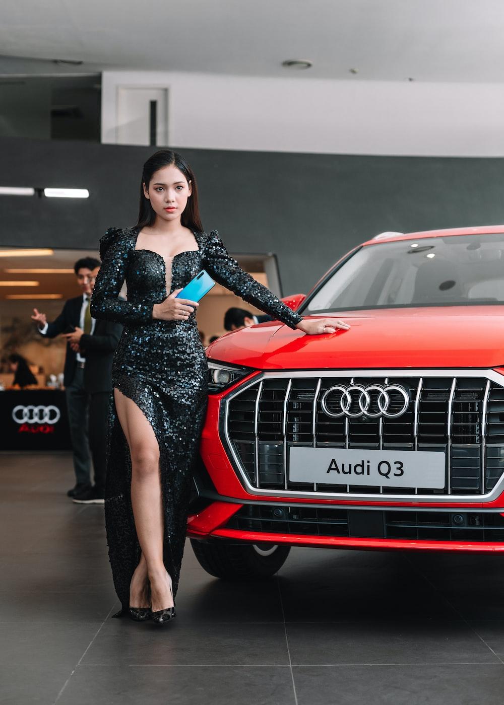 woman in black dress standing beside red audi car