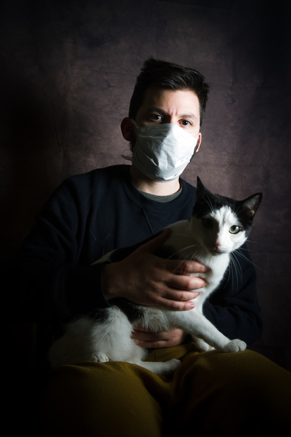 man in black long sleeve shirt holding white and black cat