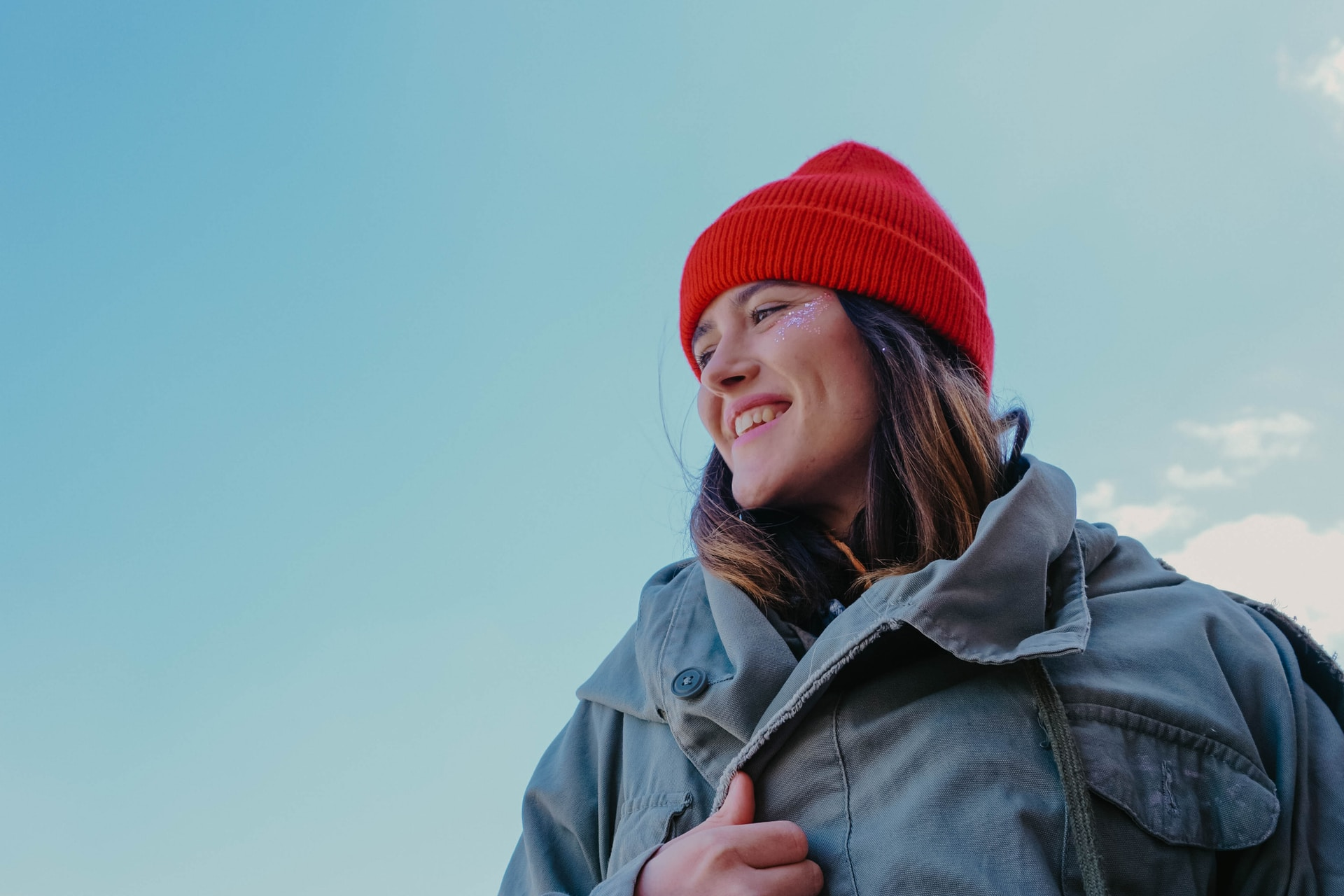 woman in gray jacket and red knit cap