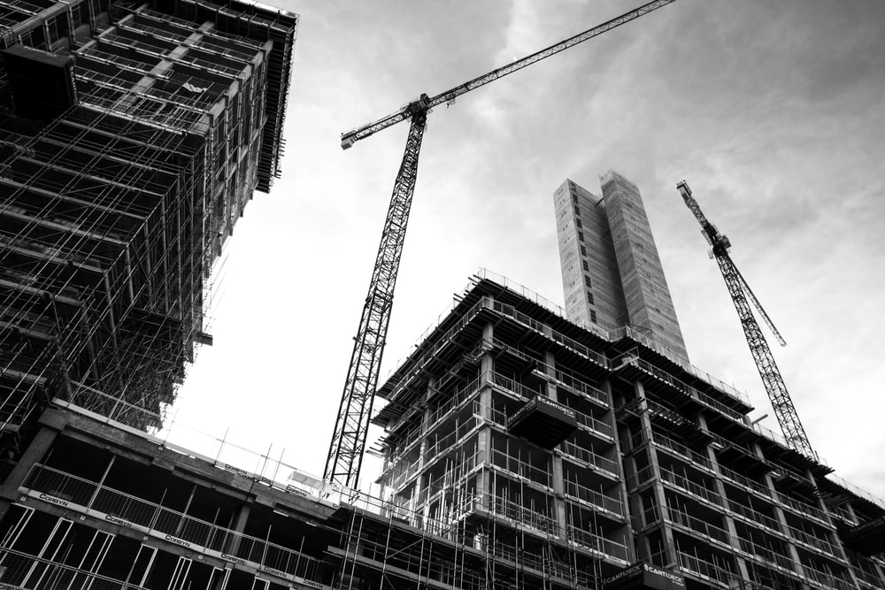 grayscale photo of crane in front of building
