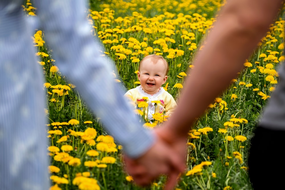 girl in white shirt standing on yellow flower field during daytime