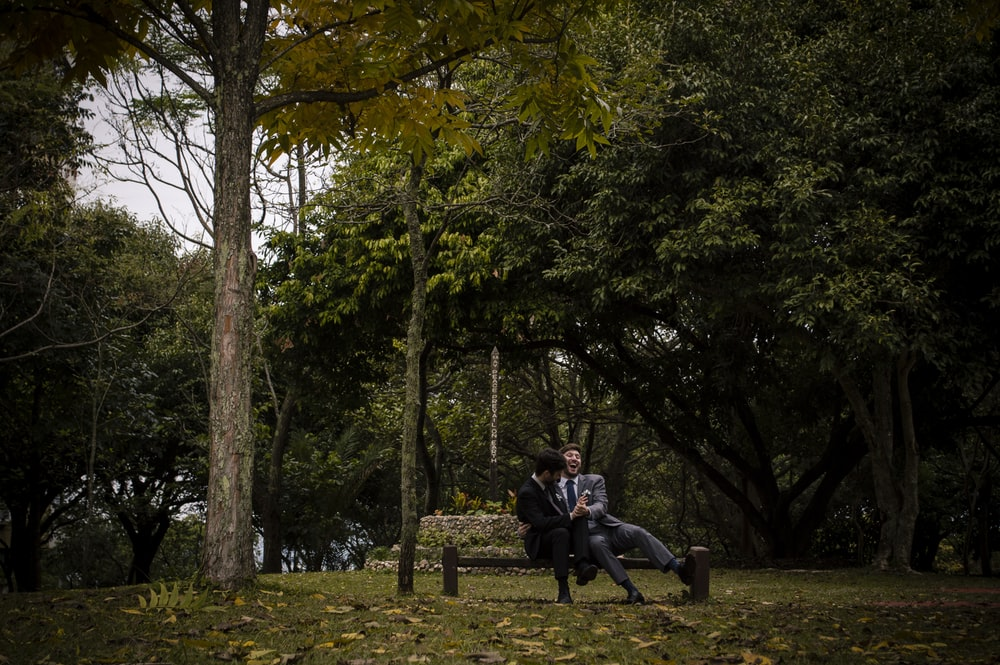 man in black jacket sitting on brown wooden bench near green trees during daytime