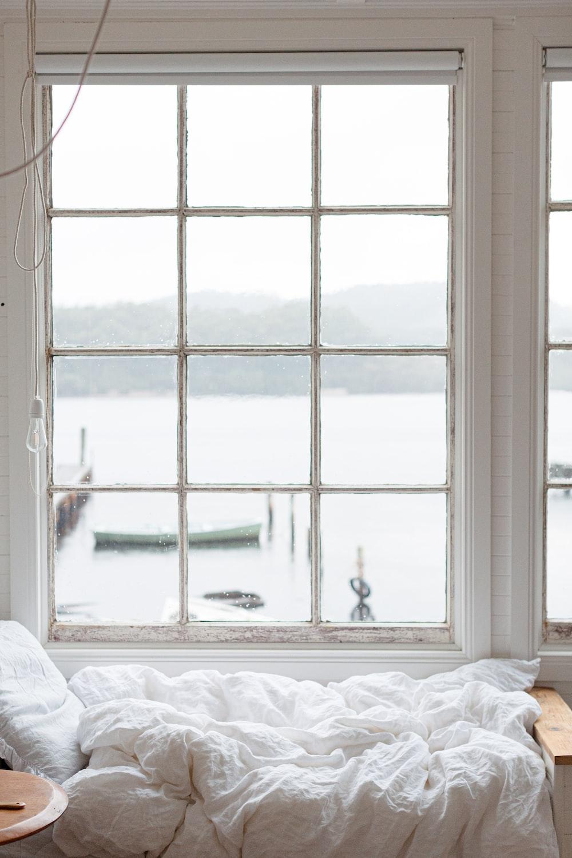 white bed near white framed glass window