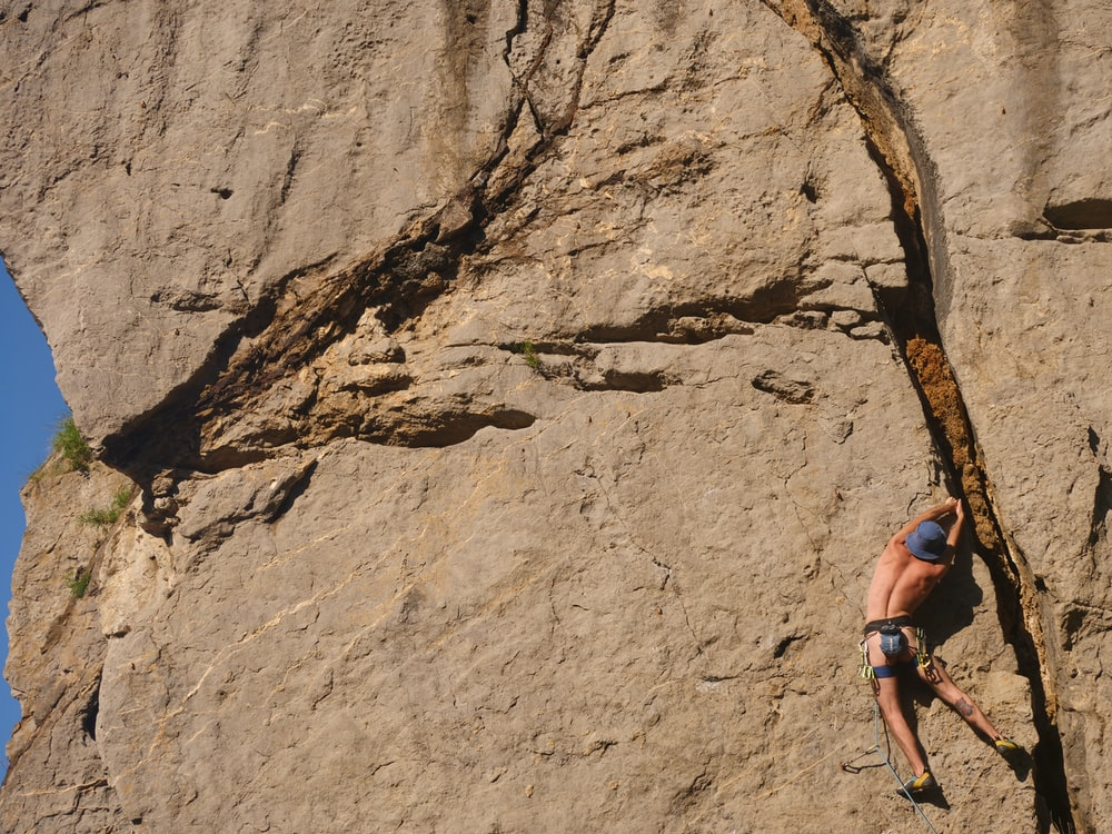 woman in blue tank top climbing on brown rock mountain during daytime