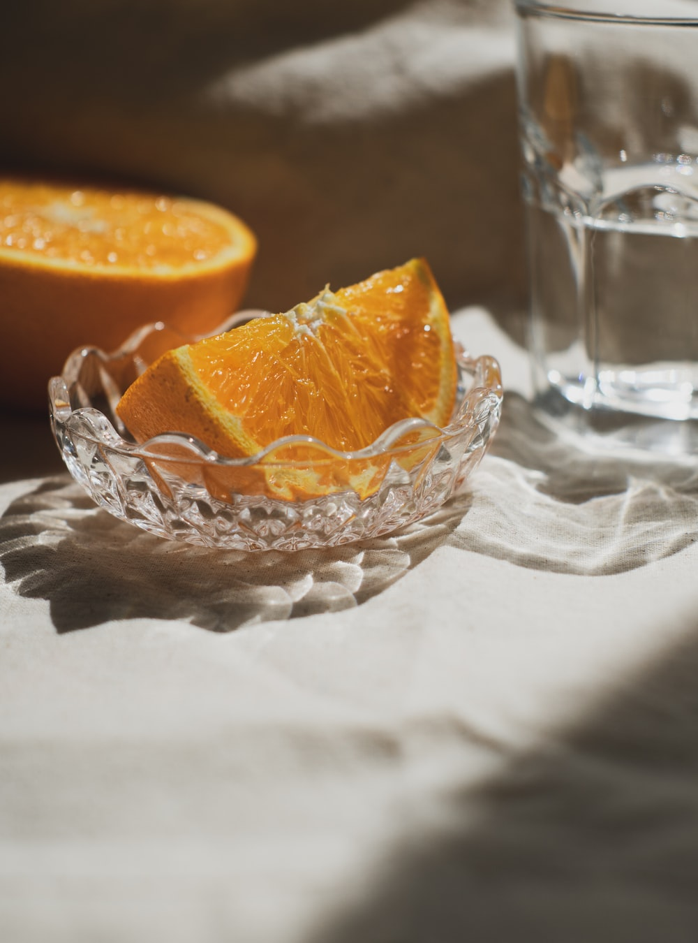 sliced orange fruit in clear cut glass bowl