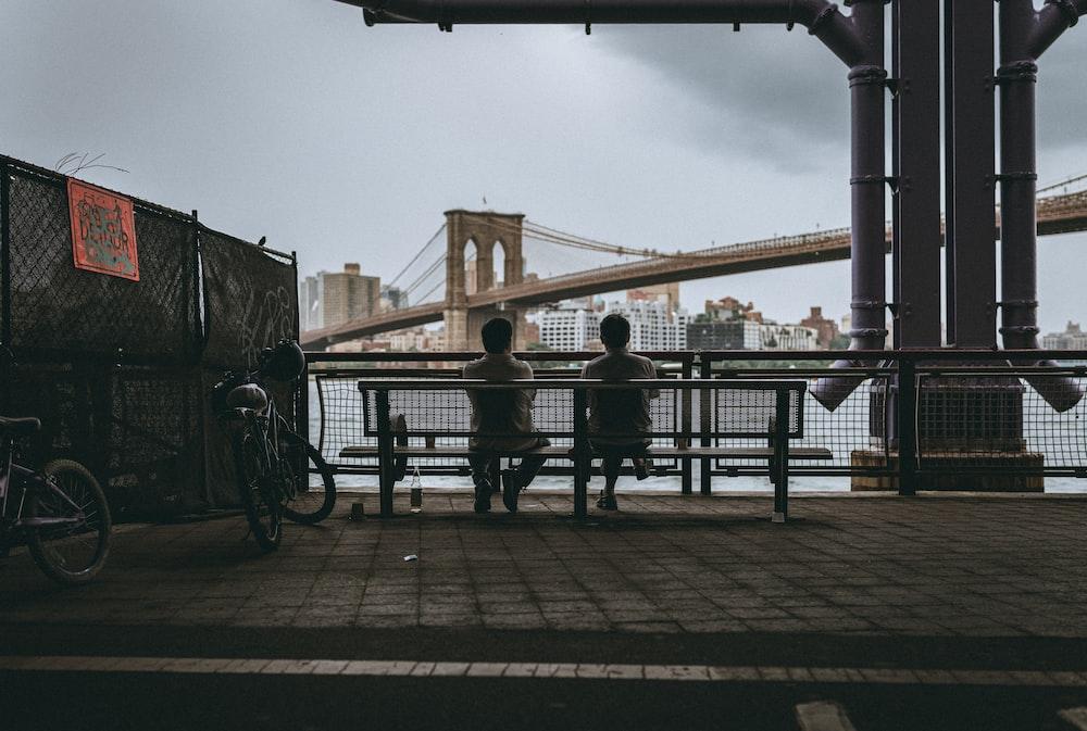 people sitting on bench near bridge during daytime