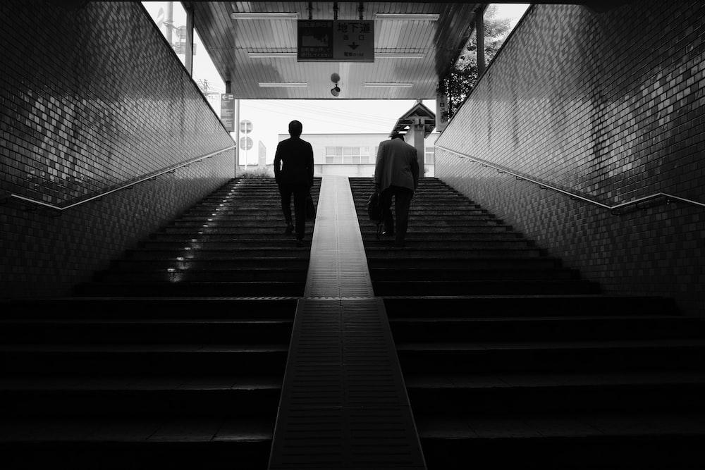 grayscale photo of people walking on the hallway