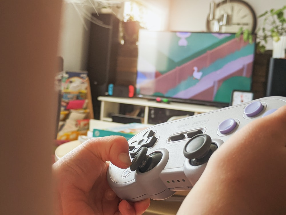 person holding white and black xbox one game controller
