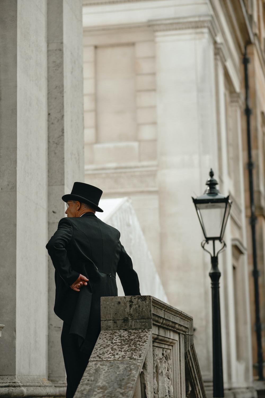 man in black coat standing near black street lamp during daytime
