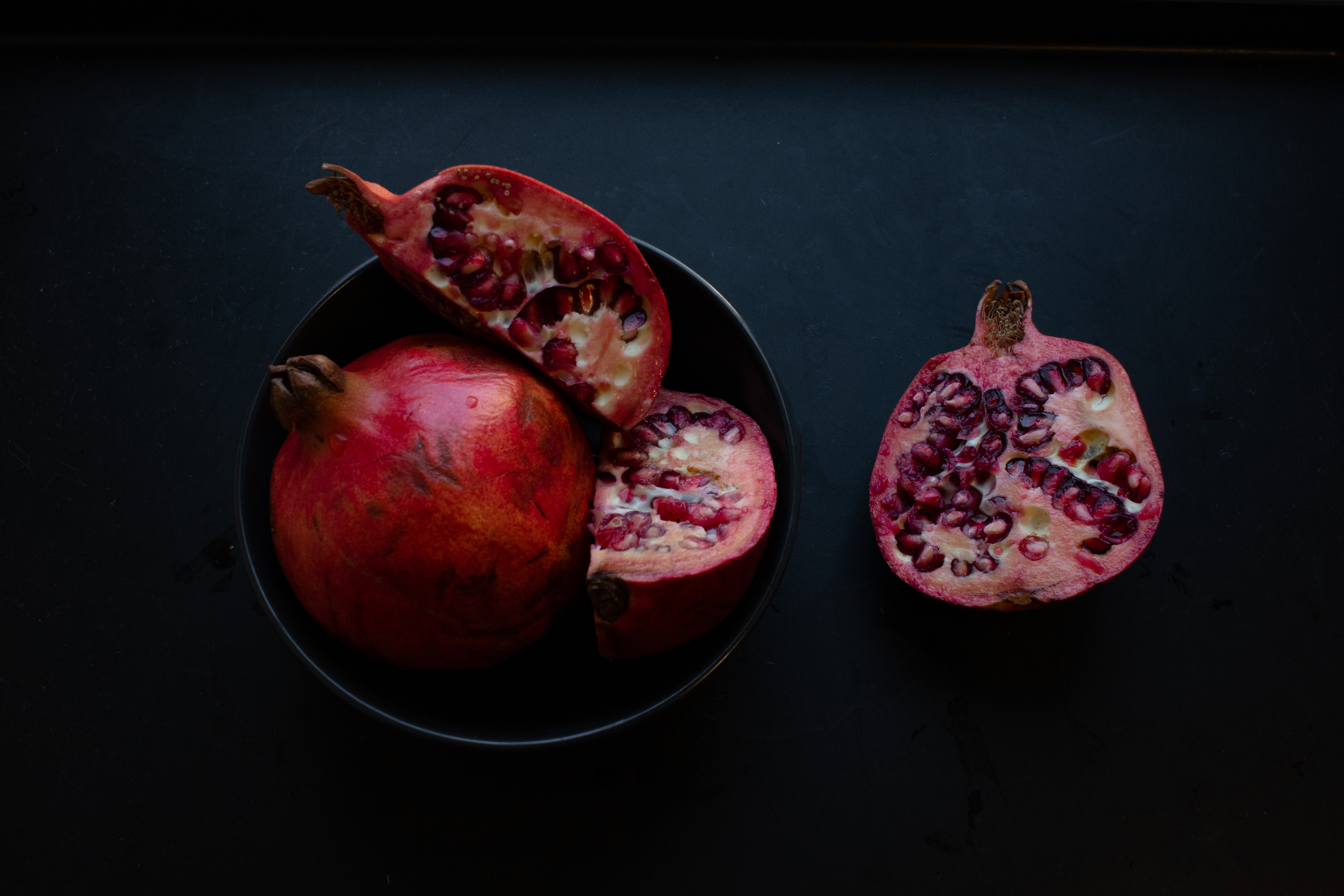 two red pomegranate fruits on black surface