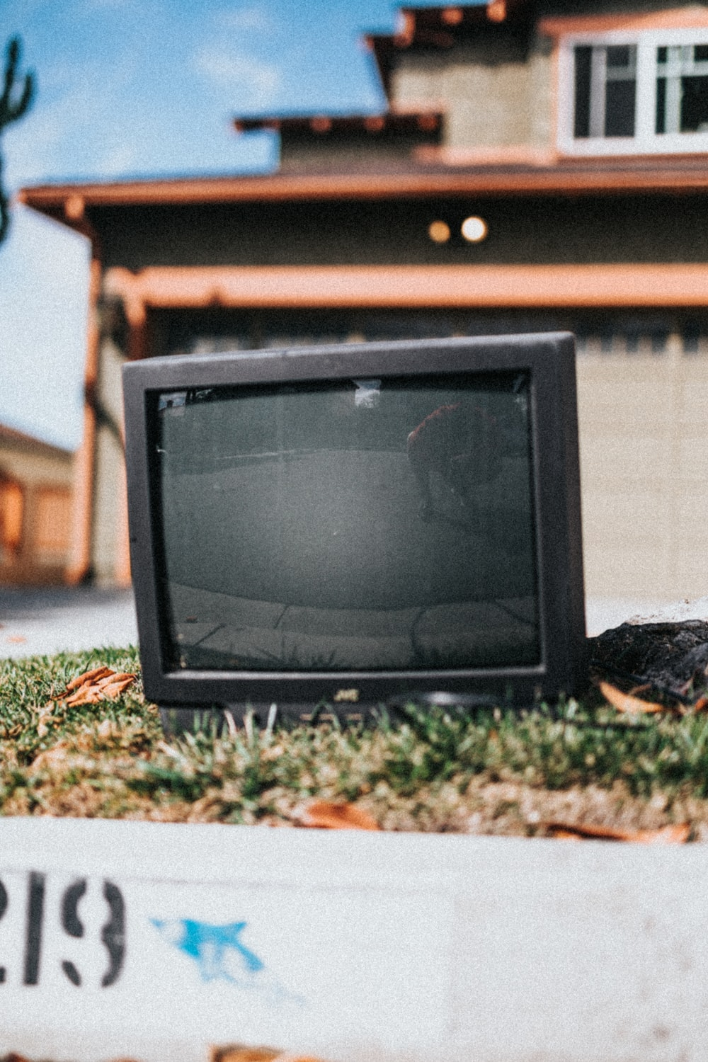 black crt tv on green grass during daytime