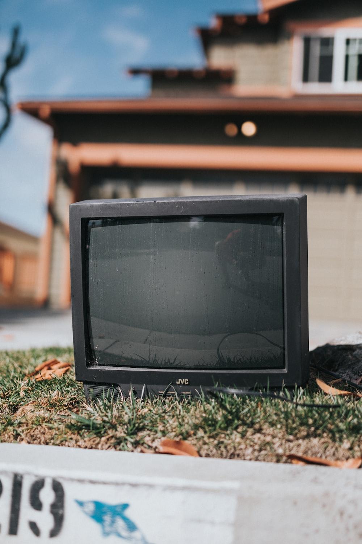 black crt tv on brown dried leaves