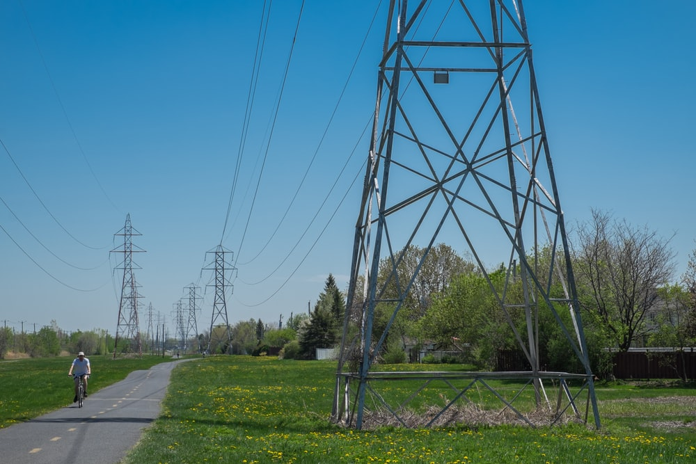 gray metal tower near green grass field under blue sky during daytime