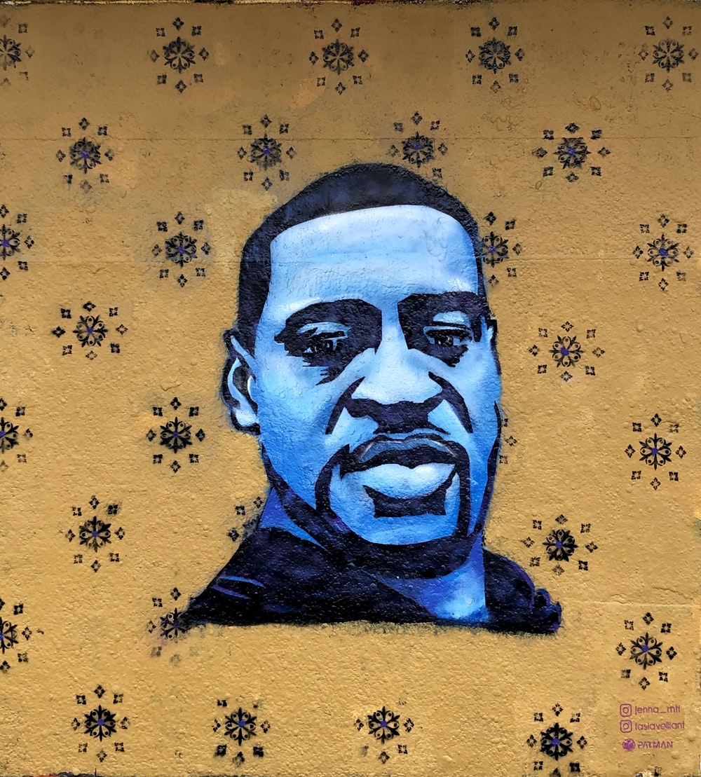 mans face on blue and white floral textile