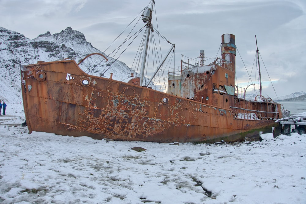 brown ship on white snow covered ground during daytime