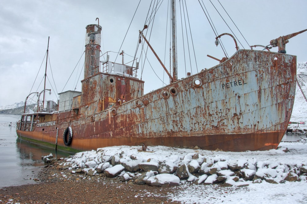 brown and white ship on brown sand during daytime