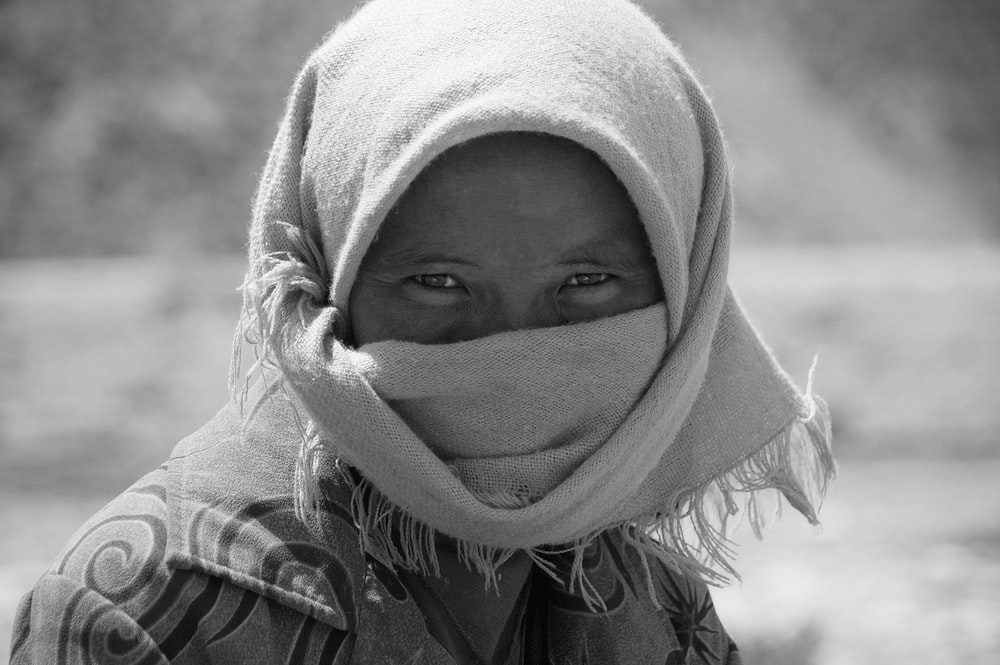 grayscale photo of woman covering her face with white towel