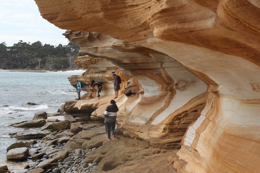 people walking on brown rock formation near body of water during daytime