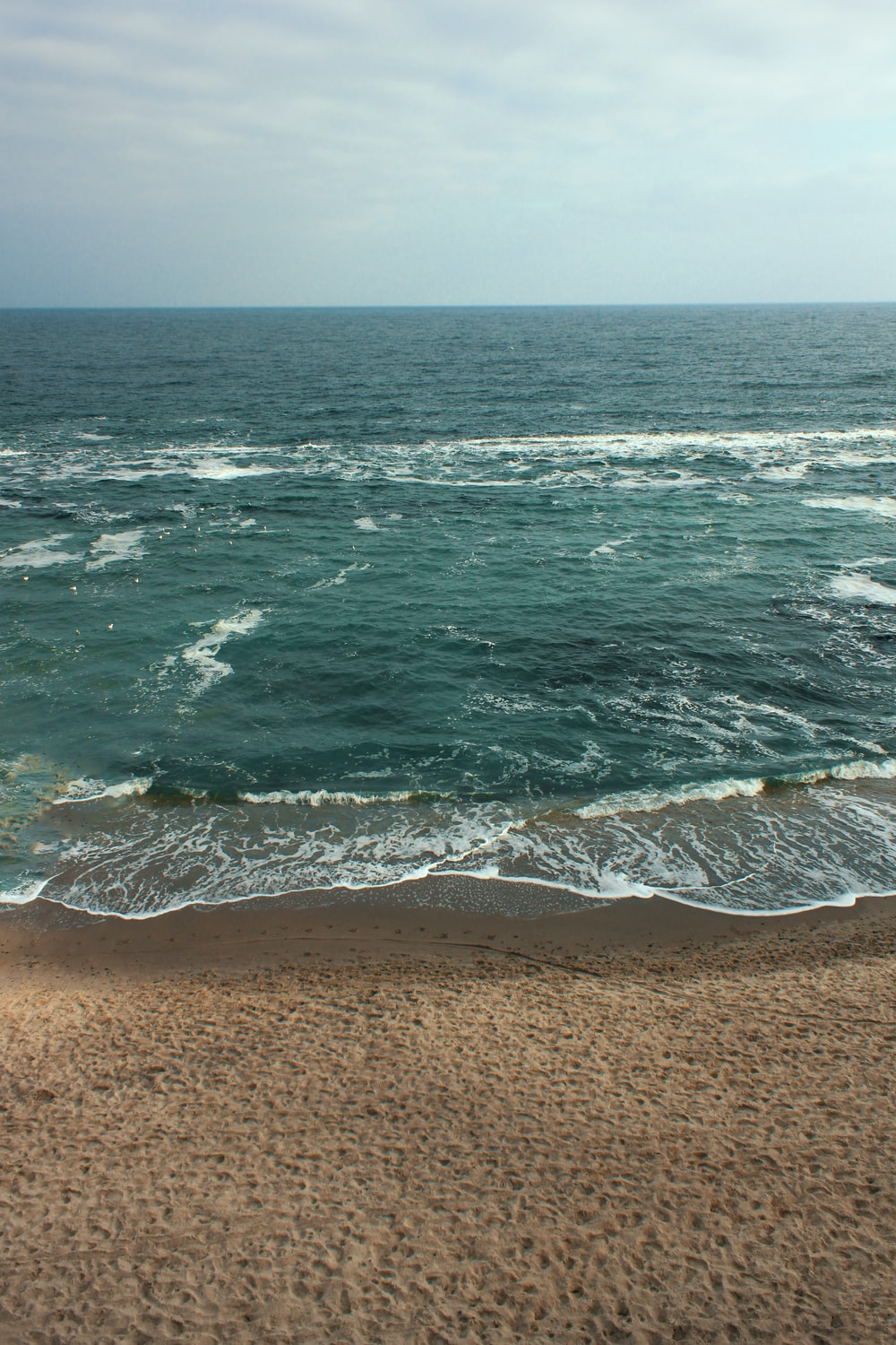 sea waves crashing on shore during daytime