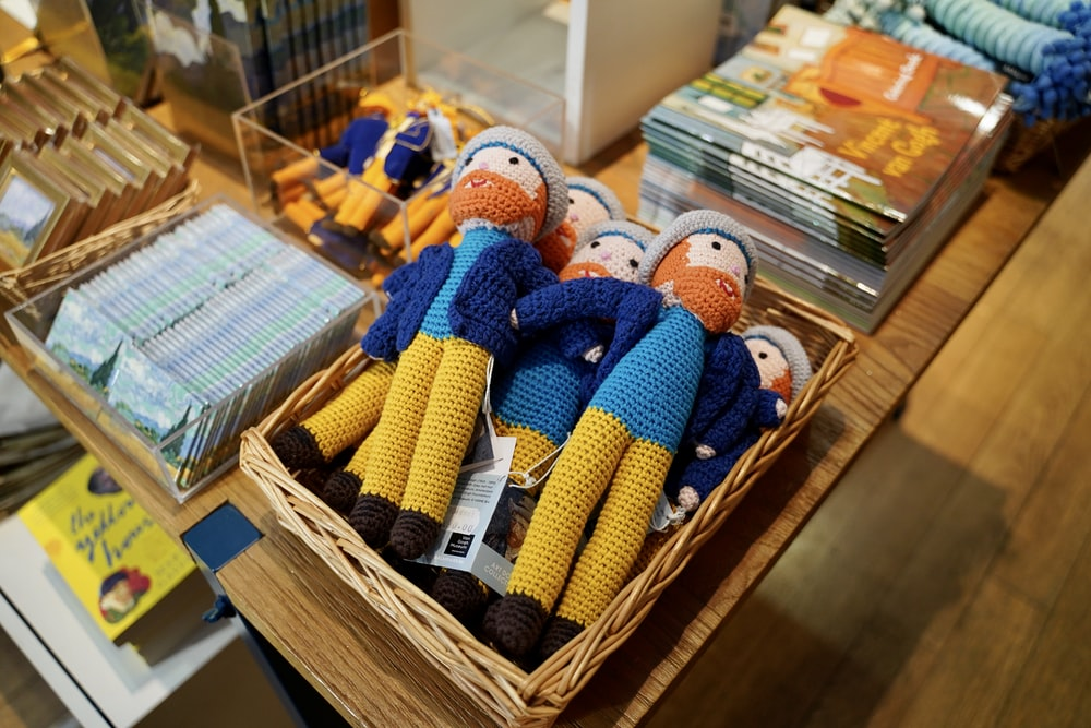 assorted knitted toys on brown wooden shelf