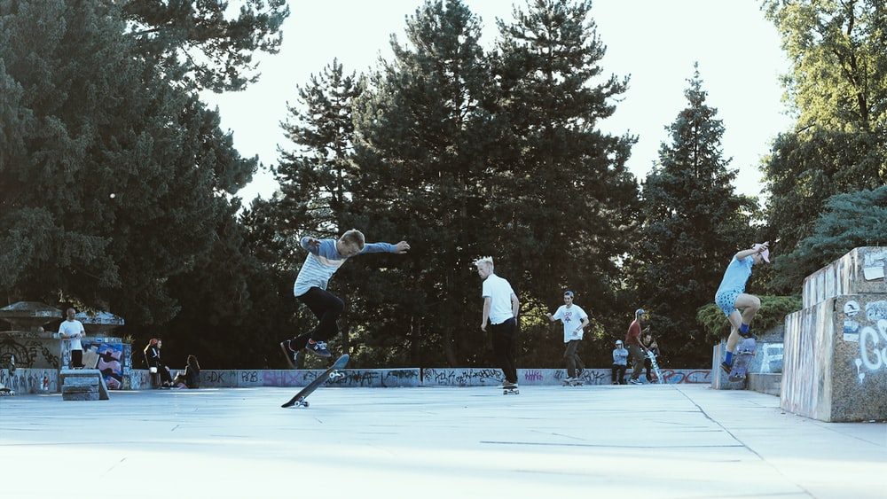 man in white jacket and black pants riding black skateboard on ice field during daytime