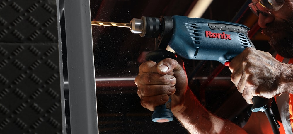 person holding blue and black cordless power drill