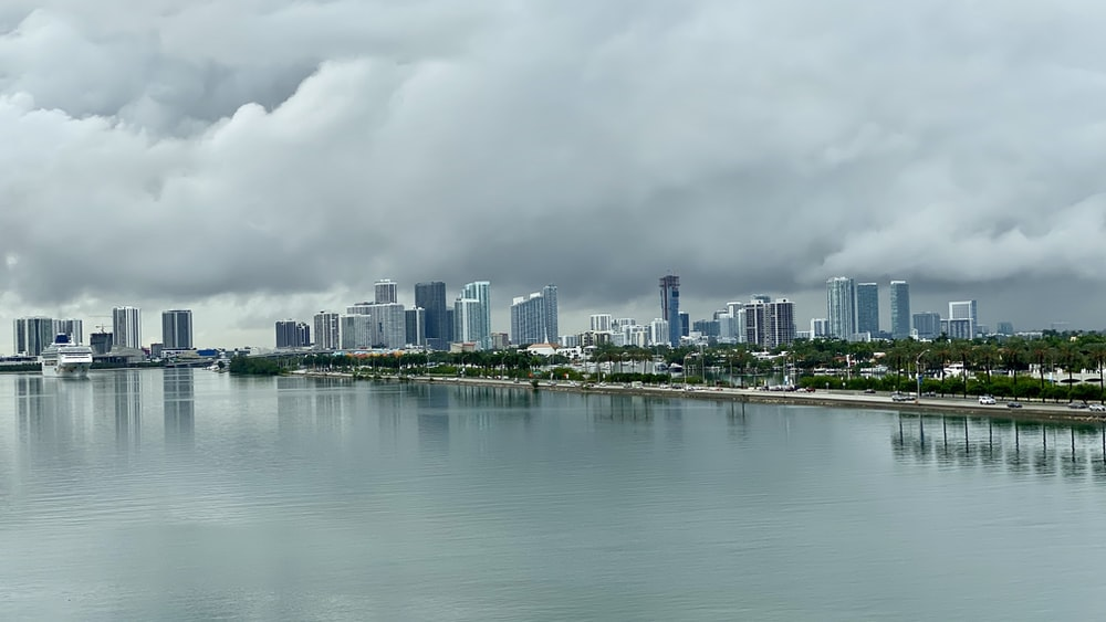 city skyline across body of water under cloudy sky during daytime