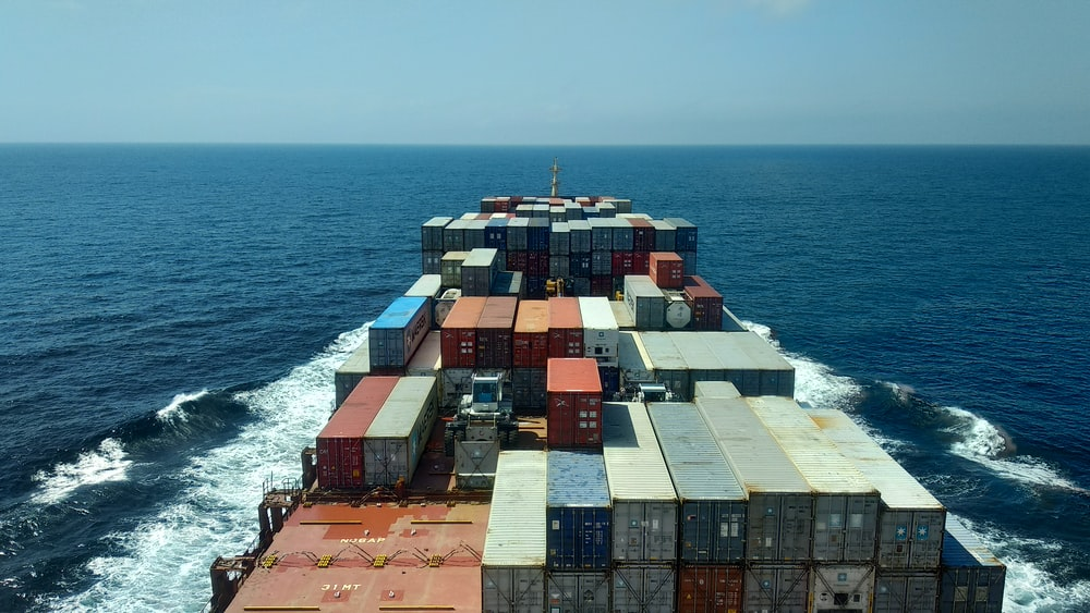 red and white cargo ship on sea during daytime