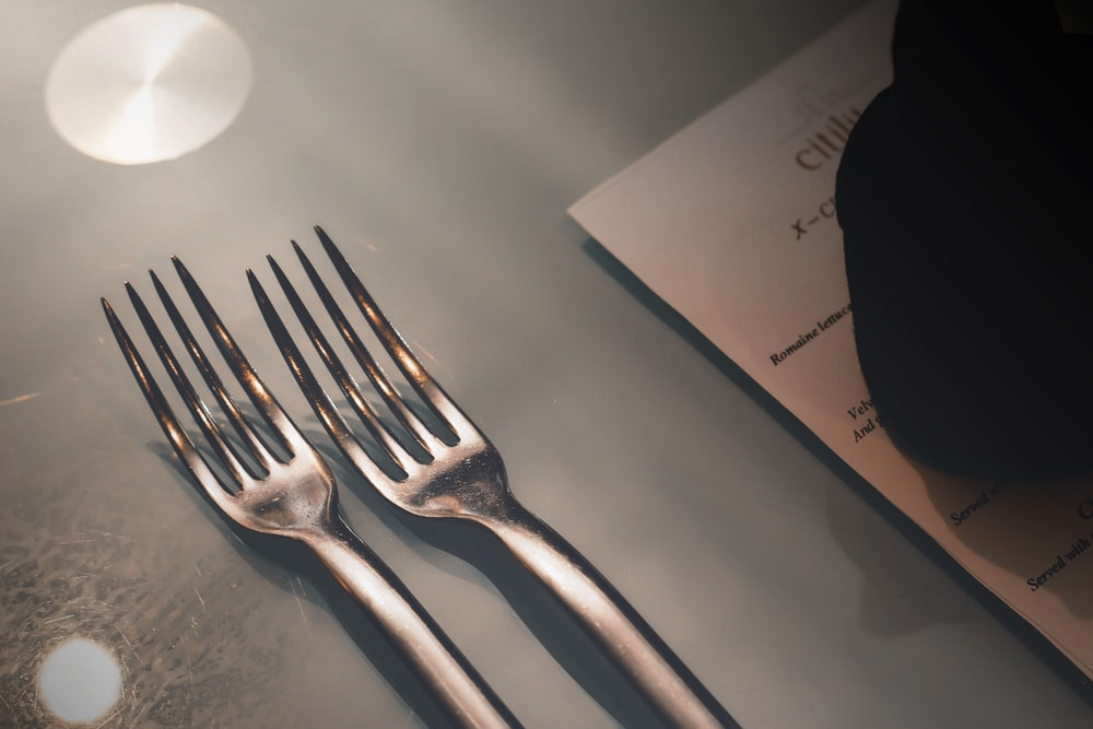 silver fork on white paper