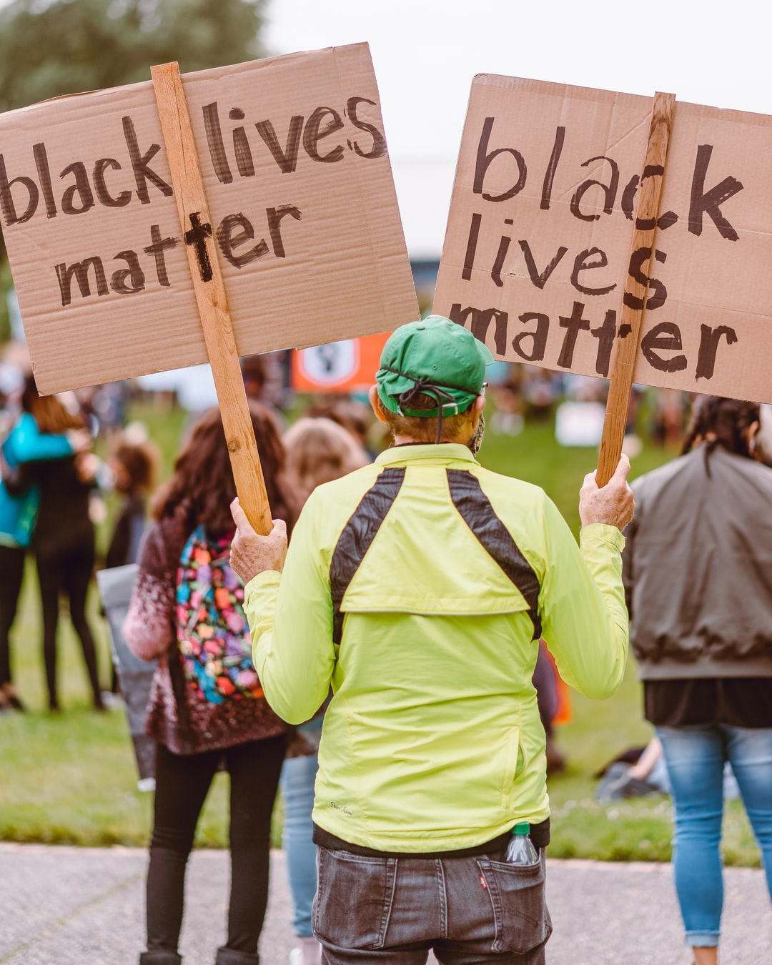 Man Holding Two Signs at Rally for BLM