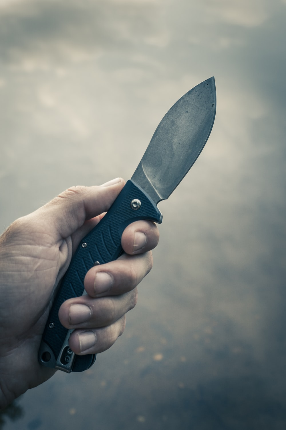 person holding black handle knife