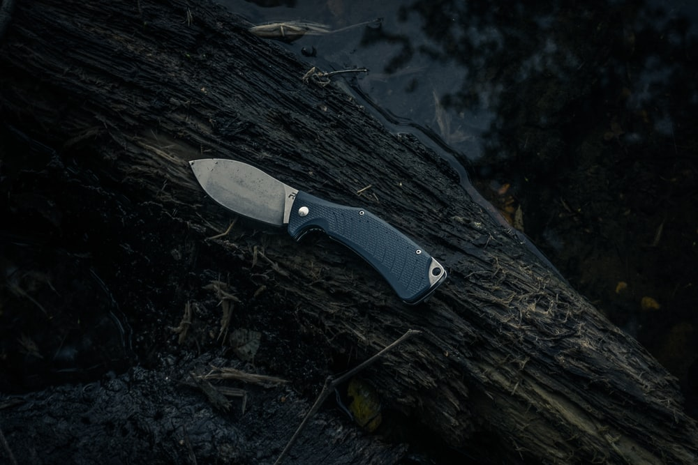 black and silver knife on brown wood