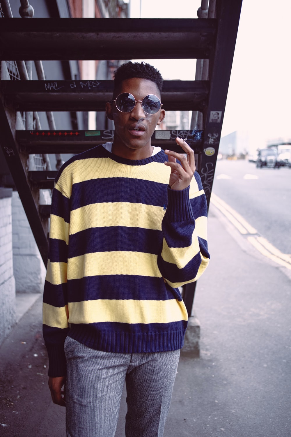 man in yellow and blue striped long sleeve shirt wearing black sunglasses