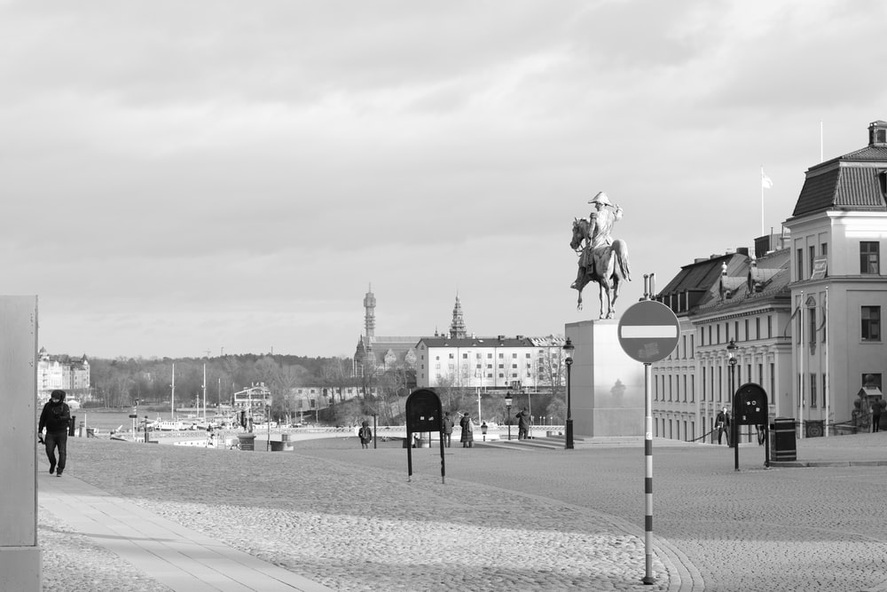 grayscale photo of man riding horse statue near body of water