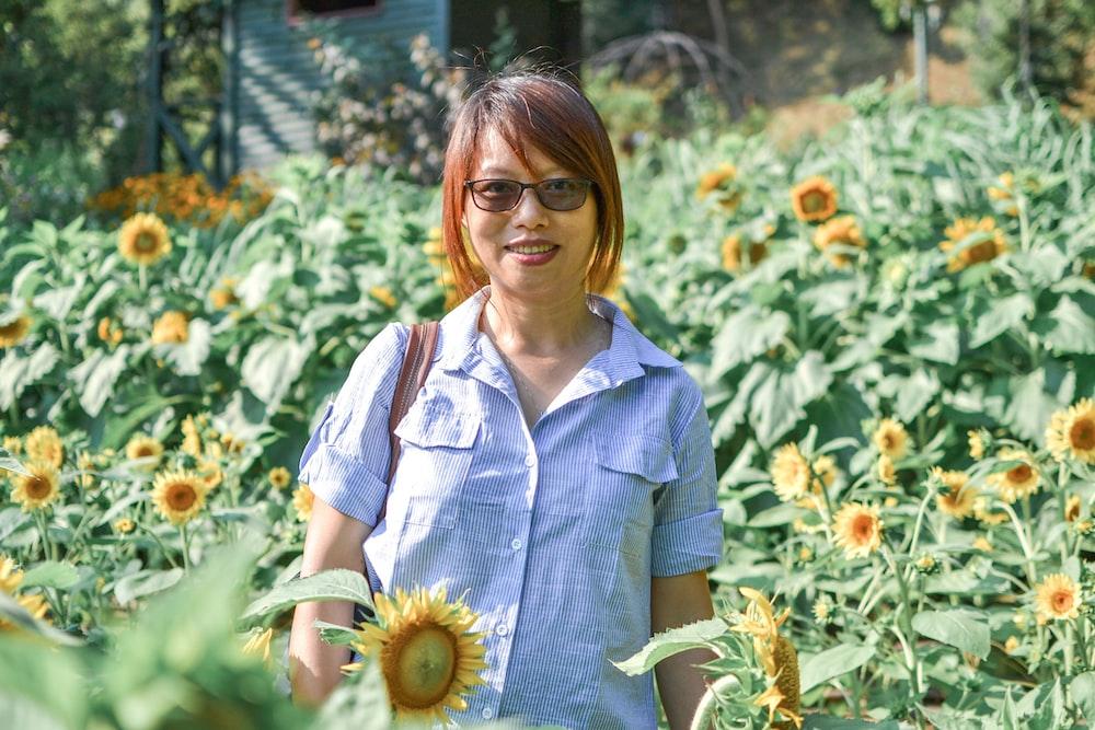 woman in blue button up shirt holding sunflower