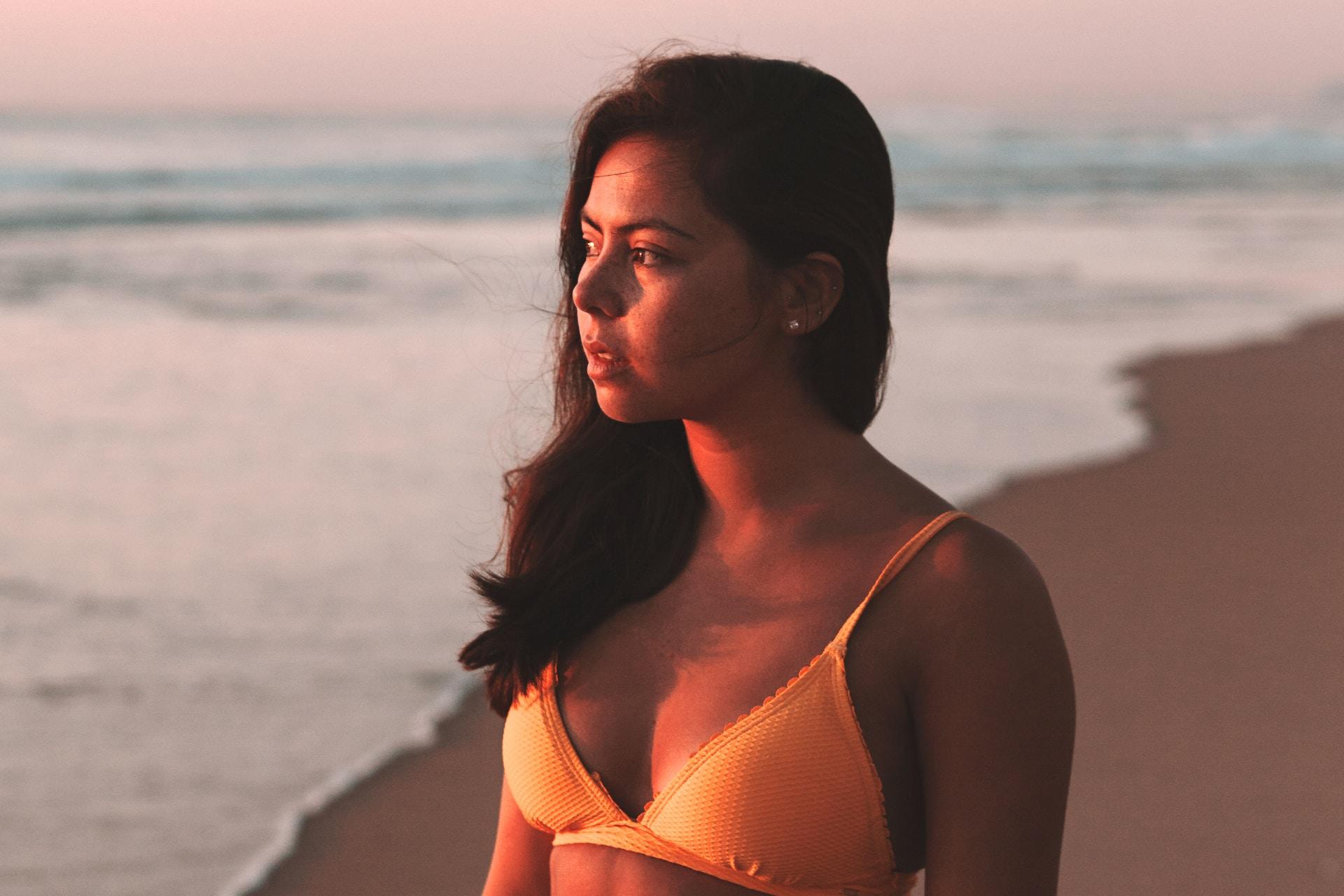 woman in white bikini top standing on beach during sunset