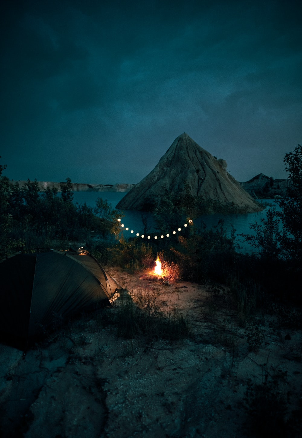 bonfire near tent and mountain during night time