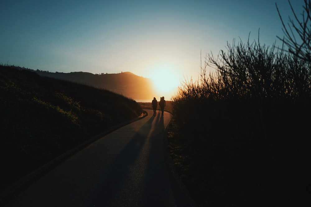 silhouette of person walking on road during sunset
