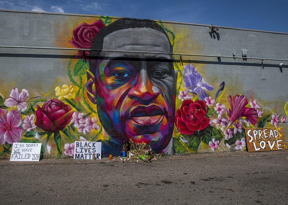 purple flower beside graffiti wall